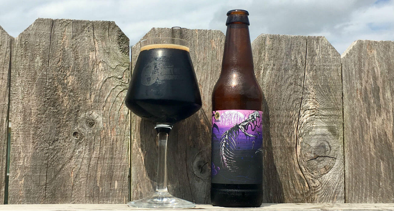 Beer-Chronicle-Houston-Craft-Beer-Review-Copperhead-Black-Venom-Full-Teku-Glass-Next-To-Bottle-On-Fence
