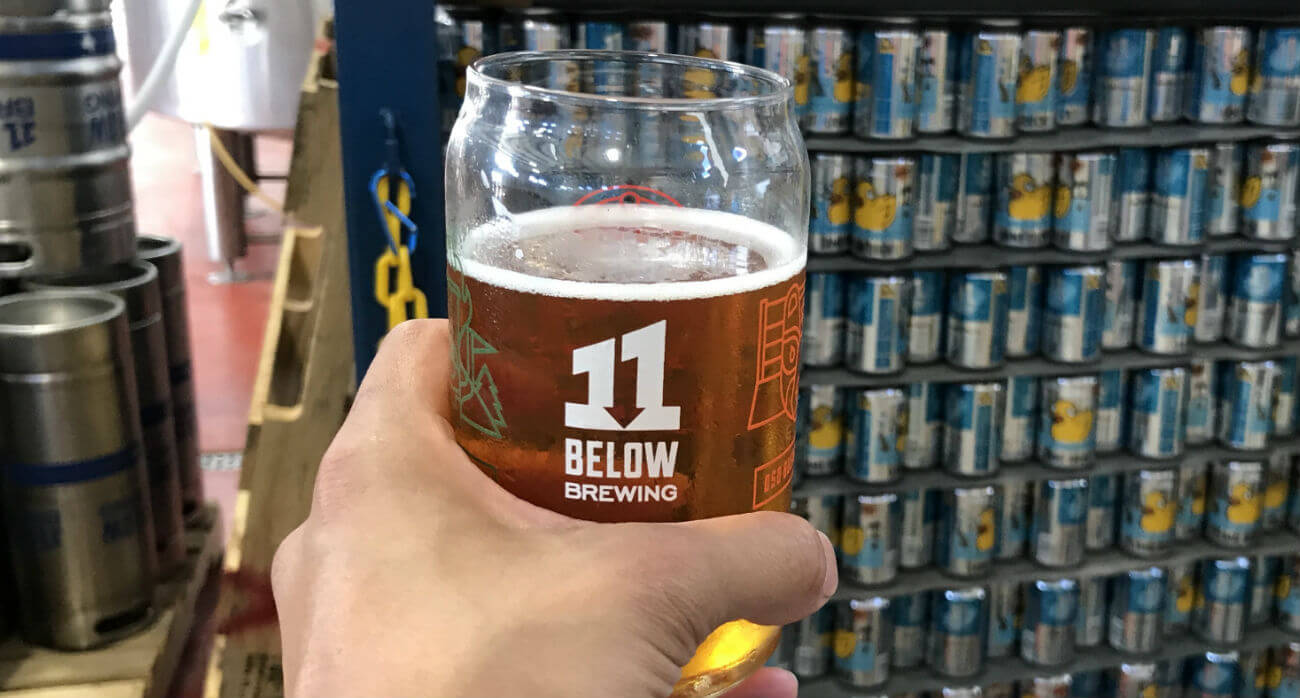 Beer-Chronicle-Houston-Craft-Beer-Review-Lame-Duck-Beer-In-Glass-In-Front-Of-Pallet-Of-Lame-Duck-Beer-Cans